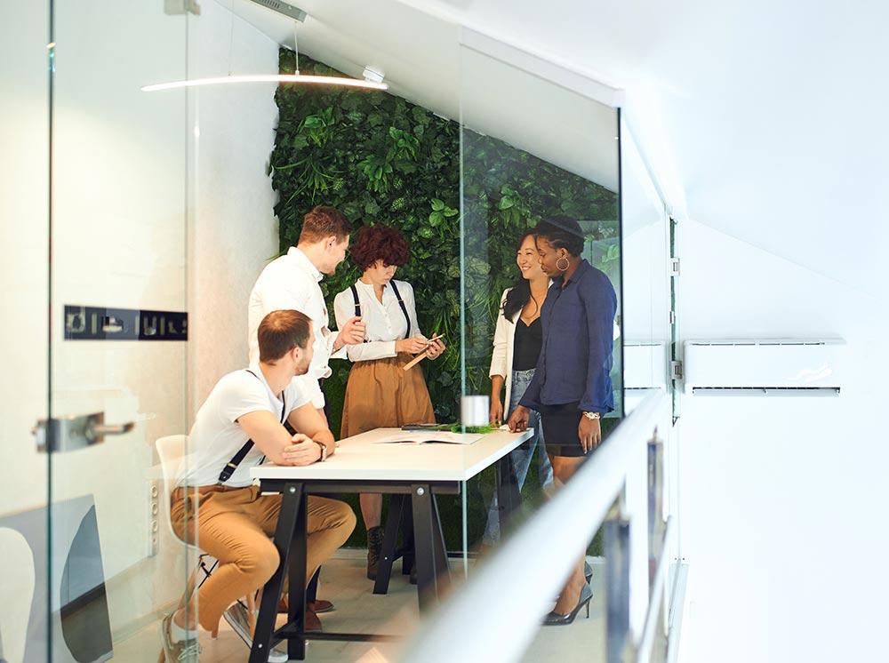 Collègues travaillant sur un projet dans un salle comportant un mur végétal