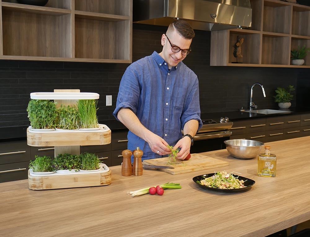 Un homme dans une cuisine au design biophilique prépare une salade de pousses récoltées du jardin novagrow